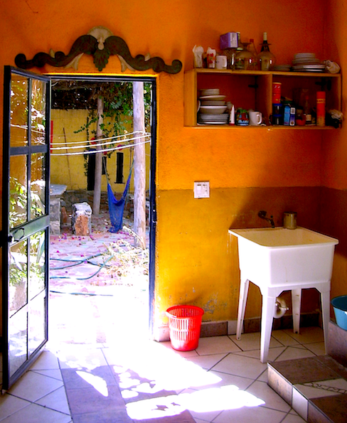 kitchen of La Casa Azul, door open to the patio, orange walls