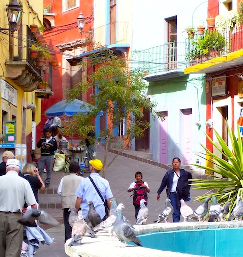 angled entrance of alley in Guanajuato with people walking and pigeons