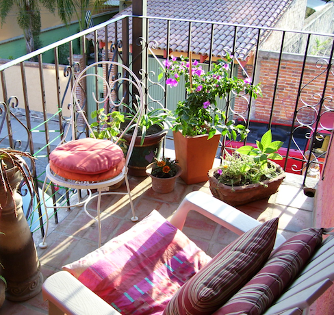 my Ajijic balcony with the chair and pots of flowers, including the terra cotta I mention with the bougainvillea