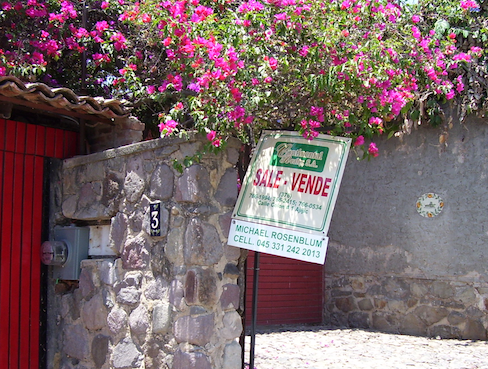 for sale sign, bougainvillea and rock wall