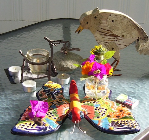 shows the altar, candles, ceramic butterfly, wooden chicken, mini bouquet of sunflower, bougainvillea and marigolds