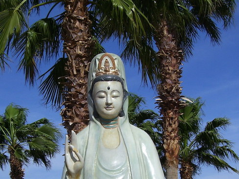 statue of quan yin with fan palms behind her