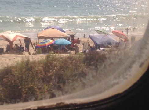 Colorful beach umbrellas north of Oceanside and small shining wave