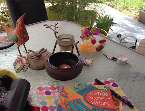 book, notebook, binoculars, candles, altar things on patio table