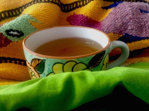 big cup of tea on bright colored blankets