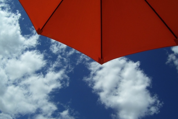 orange umbrella against blue sky with white puffy clouds